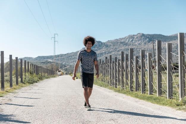 Усталый молодой бегун идет по пустой дороге