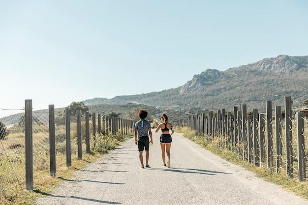 田舎道を歩いているスポーツウェアの若い人たち