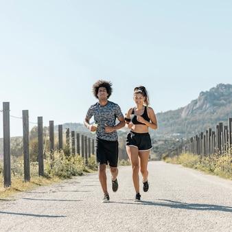 道路に沿って実行しているスポーツウェアの若いカップル