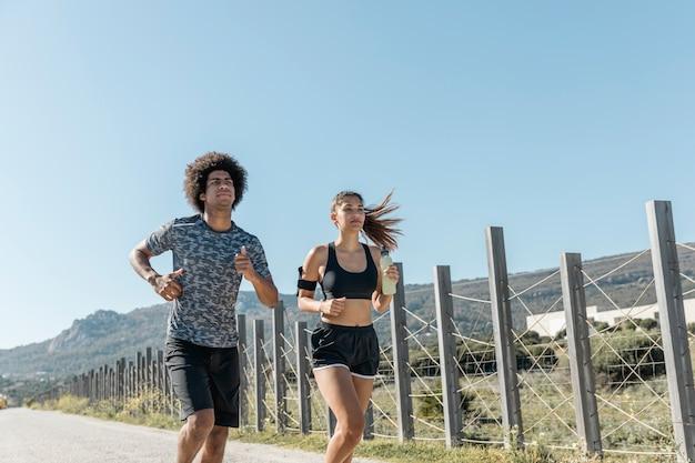Молодой мужчина и женщина бегут по дороге
