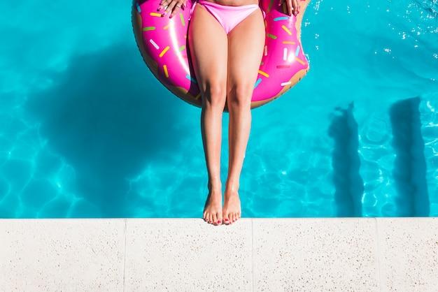 プールで膨脹可能なサークル上の女性