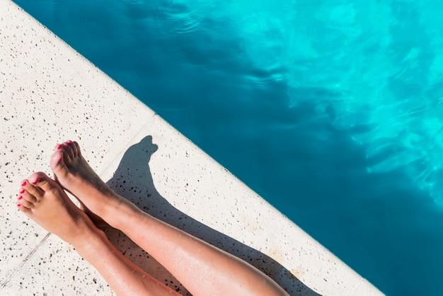 プールサイドで女性の足をトリミング