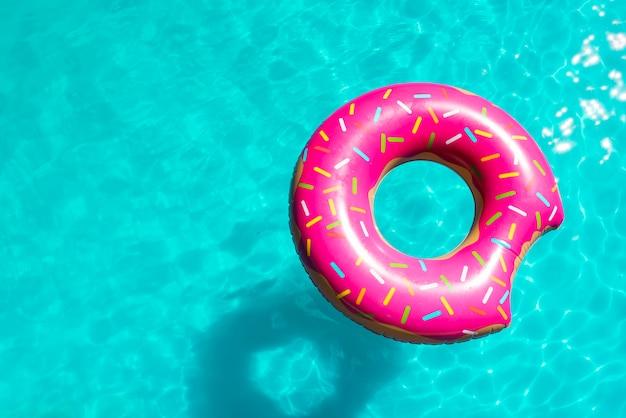 プールの明るい水の中に振りかけたインフレータブルおもちゃ
