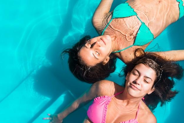 うれしそうな女友達がプールで泳いで