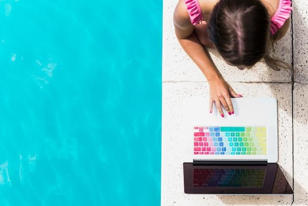 Молодая женщина, просматривая ноутбук на краю бассейна