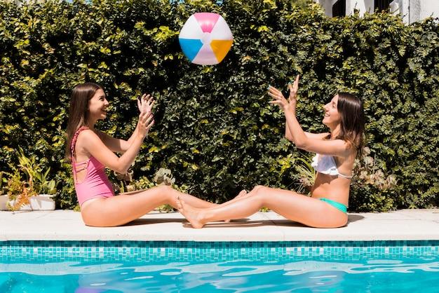 スイミングプールのそばのゴムボールで遊ぶ女性