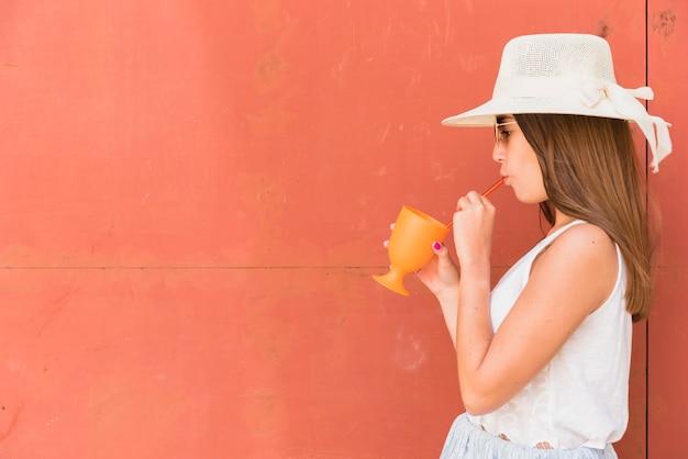 カップを押しながらわらを通して飲む帽子の若い女性