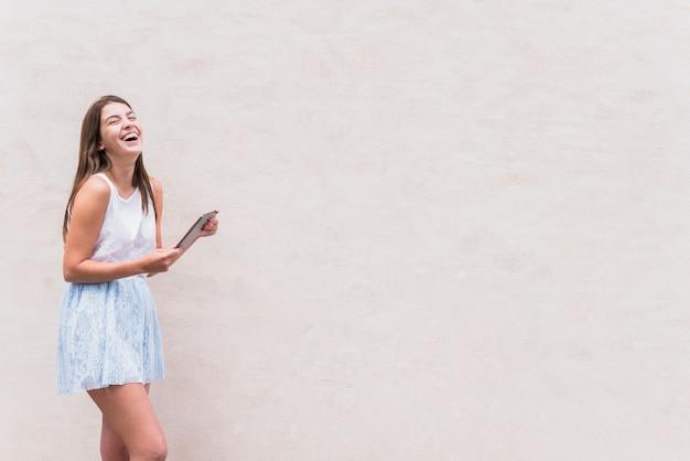 白い背景で笑っているタブレットを持つ若い女