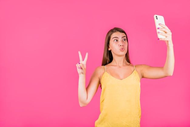 Молодая женщина, принимая селфи на розовом фоне