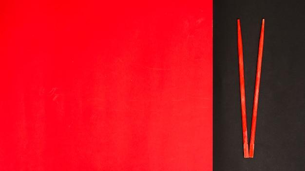 テキスト用のスペースと黒と赤の二重表面上の赤い箸