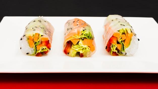 Веганские весенние рисовые бумажные рулетики с овощами на тарелке