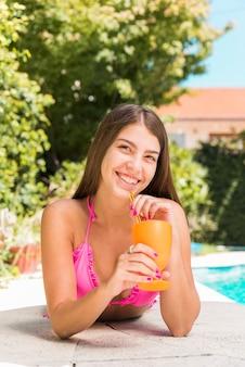 プールの端に横たわっている間ジュースを飲む女性