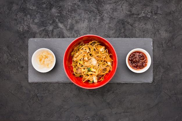Вид сверху на вкусную лапшу в миску с соусом и маринованным имбирем на черном сланцевом камне