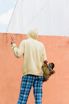 ロングボードを押しながら平和のジェスチャーを示す男