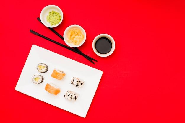 Азиатские роллы на тарелке с разными соусами и маринованным имбирем в миске