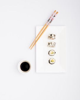 Готовые к употреблению суши роллы на белой тарелке с палочками и соевым соусом, изолированных на белом фоне