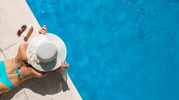 Женщина в широкополой шляпе лежит на границе бассейна