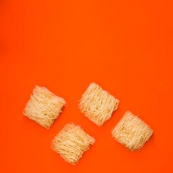 鮮やかなオレンジ色の背景上の平らな生麺
