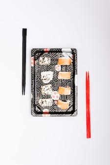 白い表面に分離された箸の近くのトレイにジューシーなサーモンの魚と寿司の高架ビュー