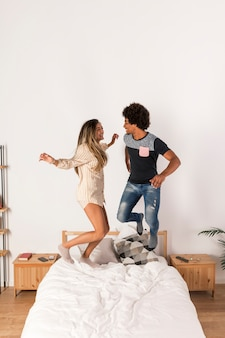 異人種間のカップルがベッドの中でジャンプの肖像画