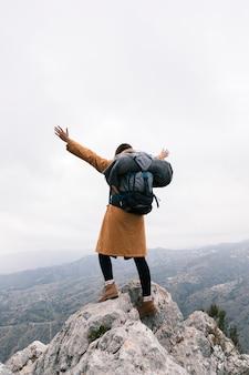 山の上に立っている彼女の腕を上げる女性の背面図