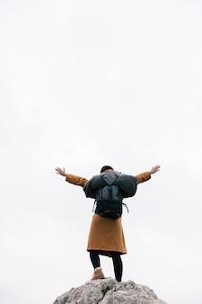 空に対して彼女の腕を上げる山の上に立っている女性の後姿