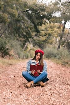 Портрет молодой женщины, сидящей на пути и читающей книгу