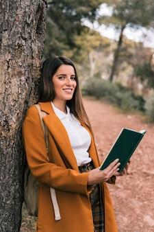 本を手に持って木にもたれて笑顔の若い女性