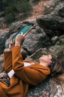 本を読んで岩の上に横たわる若い女性