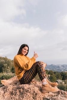 Улыбается молодая женщина, сидя на вершине горы, показывая большой палец вверх знак