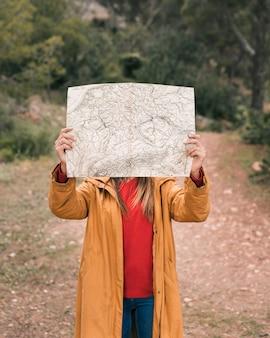 彼女の顔の前で地図を保持している若い女性