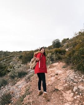 山道を歩いて彼女のバックパックを持つ女性ハイカー