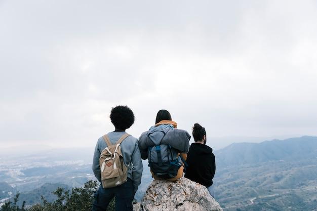 成功したハイカーの友達が山頂の景色を楽しみます