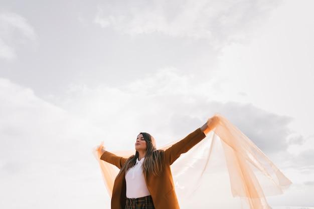 彼女の手を広げて空の下に立ってリラックスした若い女性