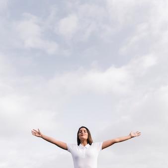 青い空を背景に彼女の手を広げて彼女の目を閉じて若い女性