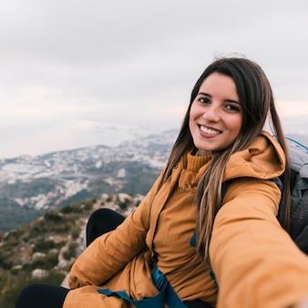 Улыбается портрет молодой женщины турист, принимая селф, сидя на вершине горы