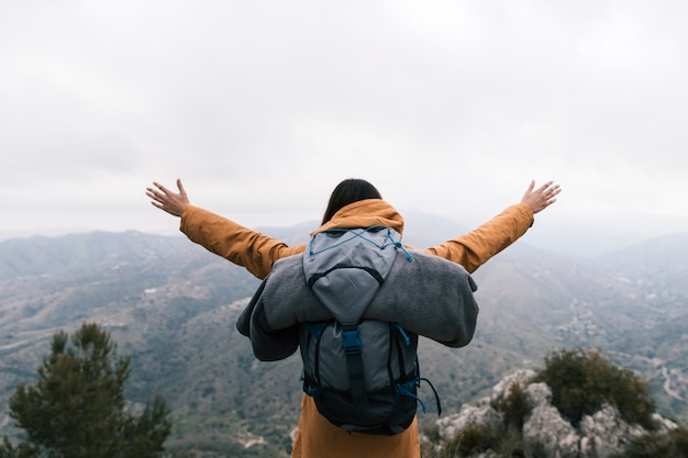自然を愛する山の上に立っている女性のバックパッカー