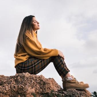 空に対して自然を楽しんでいる岩の上に座っている若い女性
