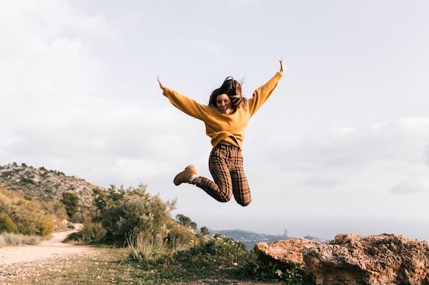 興奮した若い女性が山の上をジャンプ