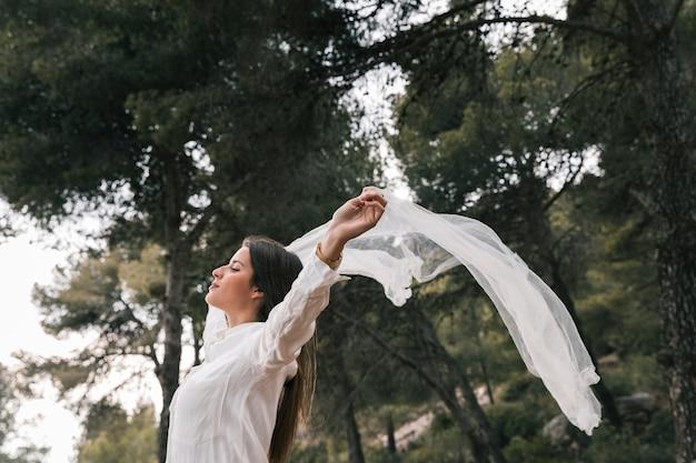 スカーフを飛んで、森の中の新鮮な空気を楽しんでいる彼女の手を上げる若い女性の側面図