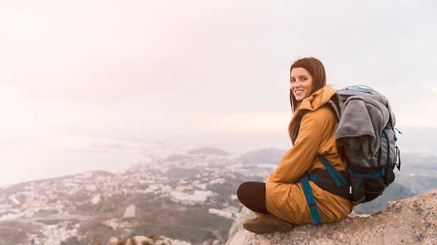 Улыбается молодая женщина, сидя на вершине горы с ее рюкзаком