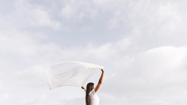 空に対して風が吹いてスカーフを保持している若い女性