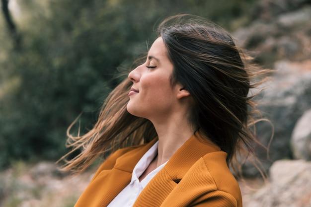 自然の中で新鮮な空気を楽しんでいる彼女の髪を投げて若い女性