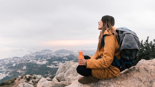 ビューを見下ろす手で水のボトルを保持している山の上に座っている女性ハイカー