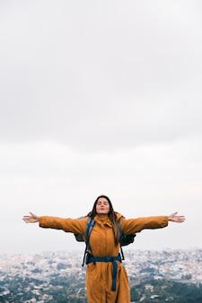 Женщина-путешественник протягивает руки, наслаждаясь свежим воздухом на вершине горы