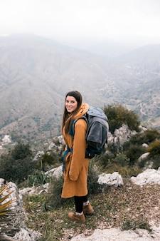 山でのハイキング彼女のバックパックと女性ハイカーの側面図