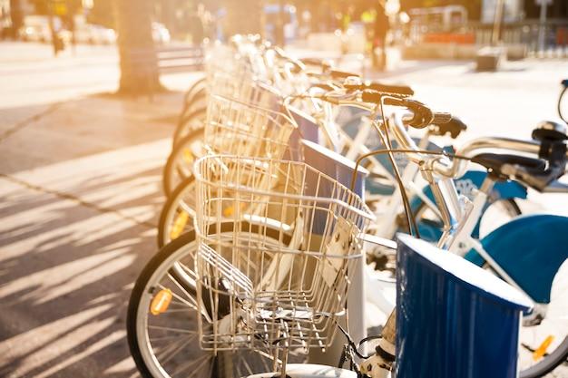 Городские велосипеды с металлической корзиной в аренду стоят в ряд на мощеной улице