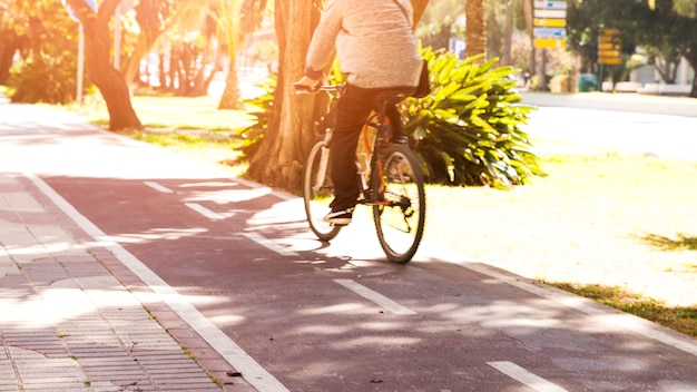 Вид сзади человека, едущего на велосипеде по велосипедной дорожке