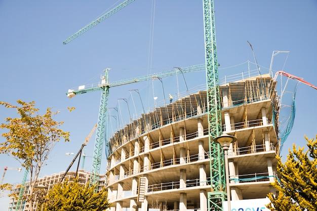 建物の前に建設用クレーンの低角度のビュー