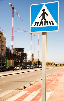 Конец-вверх предупредительного знака пешеходов в городской улице с строительной площадкой